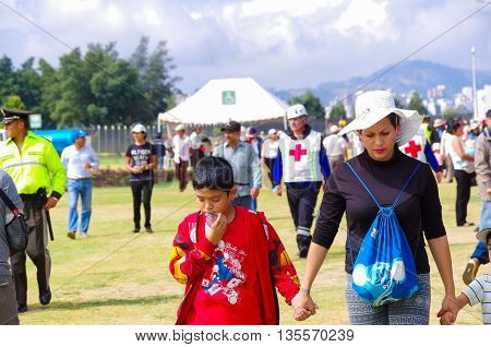 QUITO, ECUADOR - JULY 7, 2015: Selective focus for a woman with a white hat and his son in her hand. First aids and police behind.