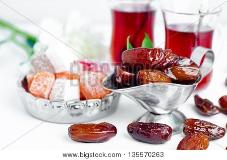Traditional arabic tea set and dried dates. Isolated white background