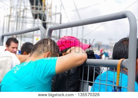 QUITO, ECUADOR - JULY 7, 2015: A young boy with blue t-shirt praying with head down, leaning against a metal fence.