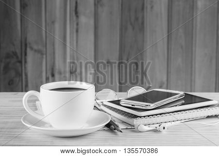 Note booksmart phonecoffee cupand stack of book on wooden table background.black and white tone