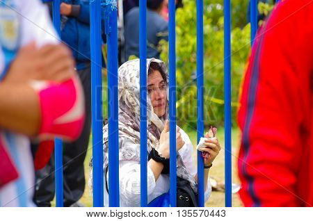 QUITO, ECUADOR - JULY 7, 2015: A woman covered her head attends to pope Francisco mass in Ecuador.