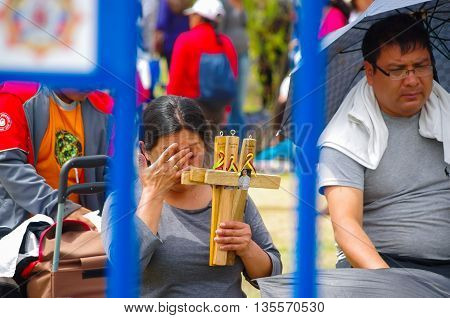 QUITO, ECUADOR - JULY 7, 2015: A woman selling wooden crosses for the mass, sunny day at pope Francisco mass in Ecuador.