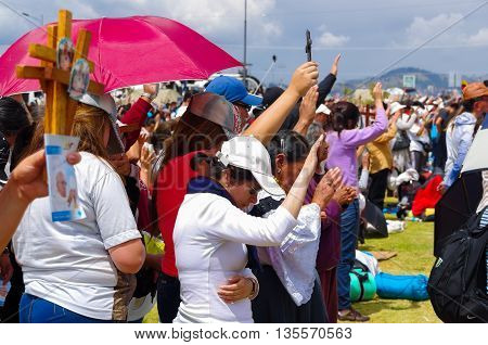 QUITO, ECUADOR - JULY 7, 2015: People raising her hands to receive pope Francisco blessings in his mass, taking care of sun.