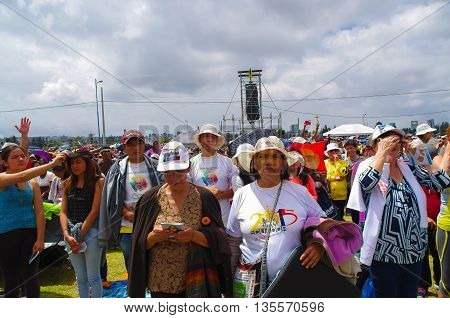 QUITO, ECUADOR - JULY 7, 2015: Unidentified people praying in pope mass event, persons with hat under the sun.