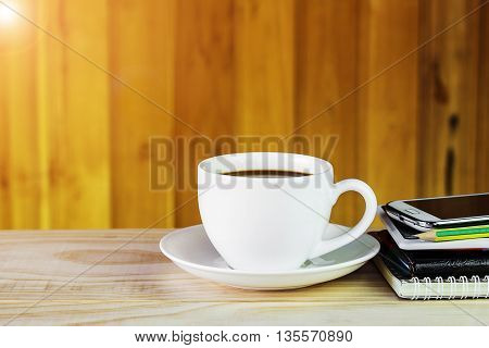 Coffee cupsmart phone and note book on wooden table background.Business concept