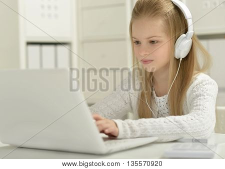 Cute little girl  in headphone with  laptop and pen at home
