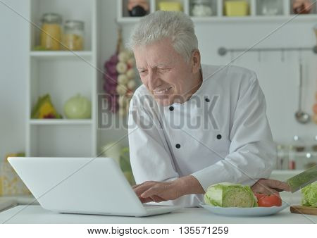 elderly male chef cooking salad with laptop