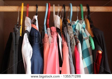 The clothes weigh on a hanger. Row of cloth hangers with shirts in the market