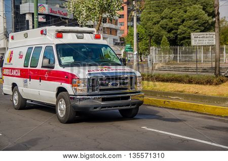 QUITO, ECUADOR - JULY 7, 2015: Ford white ambulance with red details crossing the city, emergencies only.