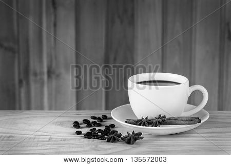 coffee cup and coffee beans on wooden table background.black and white tone