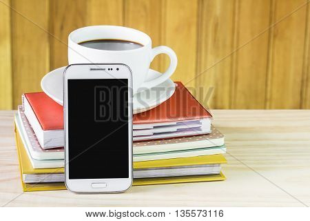 Smart phone coffee and note book on wood table background. Business concept