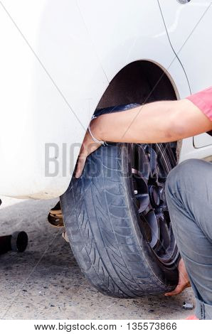 Close up shot of mechanic hands removing car wheel