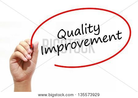 Man Hand writing Quality Improvement with marker on transparent wipe board. Business internet technology concept.