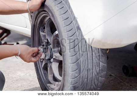 Hands of mechanic pick up the nut of car wheel and tighten