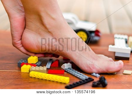 A hand making some massage on a heel of feet after stepping on colored blocks.