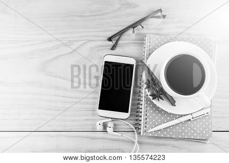 Smart phone coffeeglasses and book with white pen on wood table background. top view and business concept