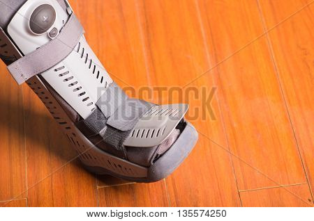 Orthopedic gray boot, when some part of the feet is affected, wooden background floor.
