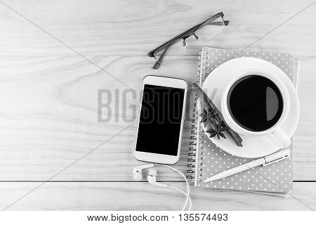 Smart phone coffeeglasses and book with white pen on wood table background. business concept.black and white tone
