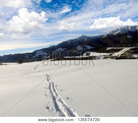 Snow path on mountain's slope in nice winter day
