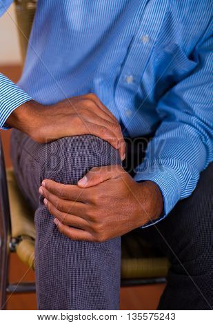 Man hands around knee, strong pain. Tshirt and pants blue.