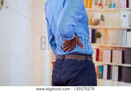 Man touching his back, back pain in office is very common.