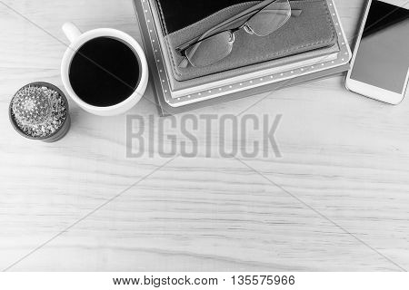 Office desk table with notebooksglasses smart phone and a cactus with cup of coffee.Top view with copy space. Business concept. black and white