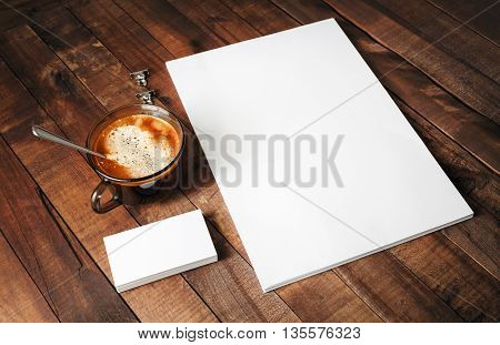 Blank paperwork template for designers. Responsive design mockup on vintage wooden background. Paper letterhead coffee cup pencil and business cards on wooden table background.