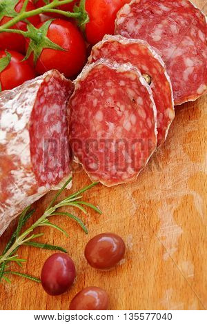 Gourmet food - salami olives and rosemary herbs closeup