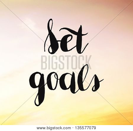 Set goals written on sunset
