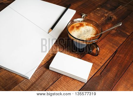 Photo of blank stationery. Blank branding template on vintage wooden table background. Blank letterhead coffee cup and pencil. Mock-up for your design.