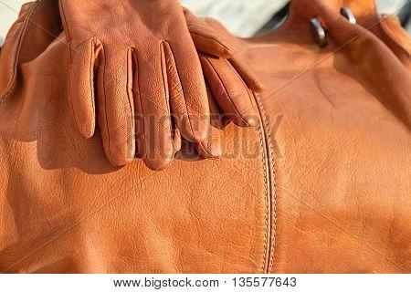 orange leather gloves lie on the bag