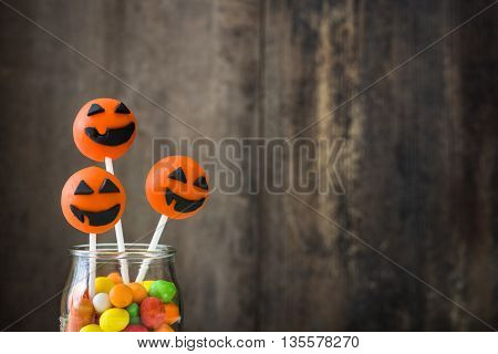 Halloween cake pops and colored candies on a rustic wooden background