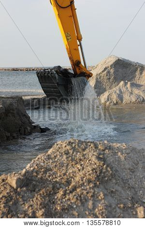 excavator loading dumper truck with sand at construction site