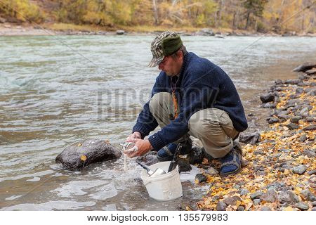 man washing dishes in the river water