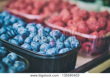 Fresh blueberry and raspberry in plastic box at market, local food healthy background in vintage hipster style