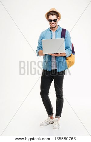 Happy handsome young man with backpack standing and using laptop