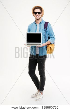 Full length of smiling young man with backpack standing and holding blank screen laptop