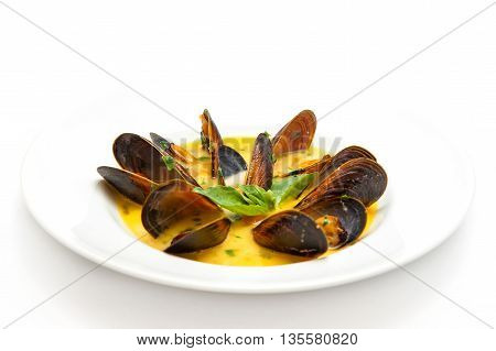 soup in a white plate of seafood with mussels and basil