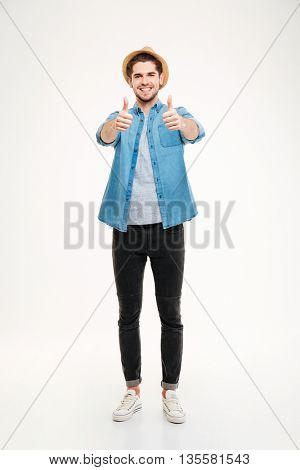 Full length portrait cheerful young man showing thumbs up isolated on a white background
