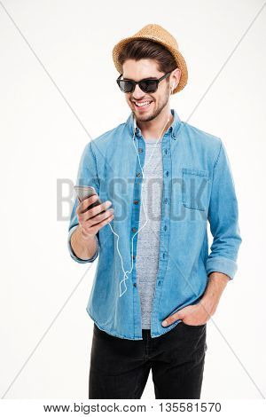 Cheerful young man in sunglasses and hat standing and using smartphone