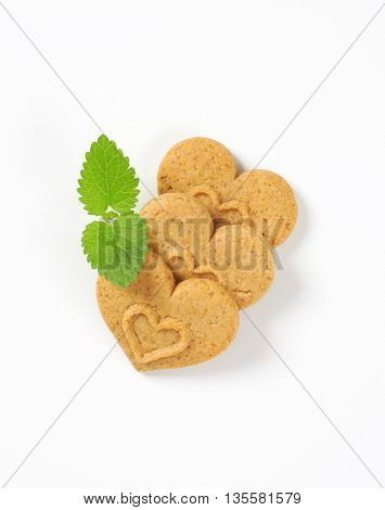 three heart-shaped cookies and mint on white background