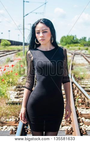 Knee portrait of young beautiful girl in black dress and nylons walking down rail tracks, cargo wagons and poppies in background