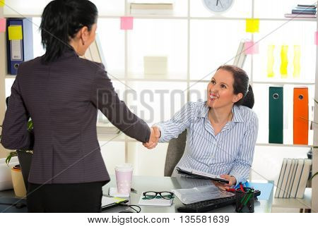 Two women chat to each other in the office. Selective focus