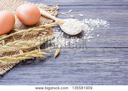 Ears of wheat and egg on a dark wooden table background