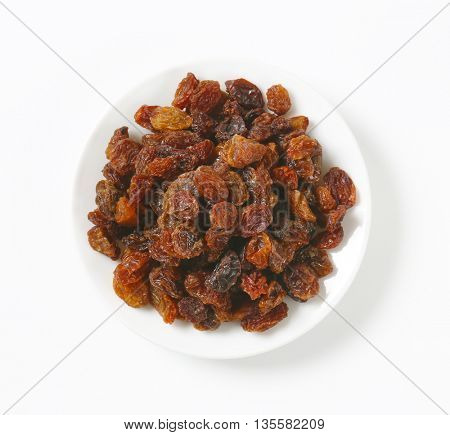 plate of raisins on white background