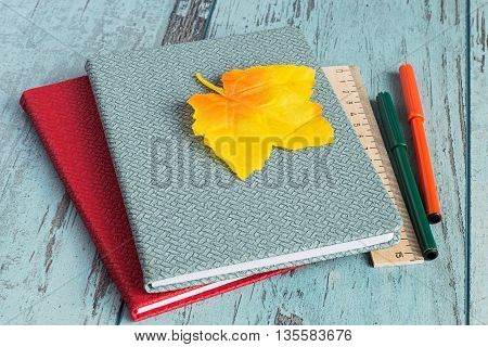 Two exercise book, pens and ruler on blue wooden background.