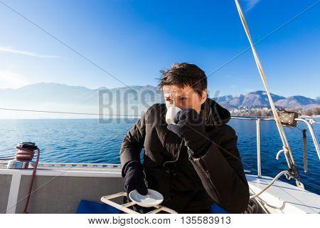 woman makes a coffee break aboard his sailboat