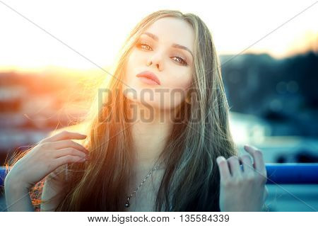 Outdoor portrait of young pretty sexy woman with magic eyes sending air kisses posing at roof at the end of bright sunset. Lovely soft back light.