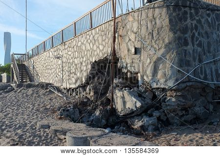 BALI INDONESIA - JUNE 23: The sea wall of a tourist restaurant and hotel lies damaged by freak waves and severe coastal erosion due to climate change on June 23 2016 in Seminyak Bali Indonesia.