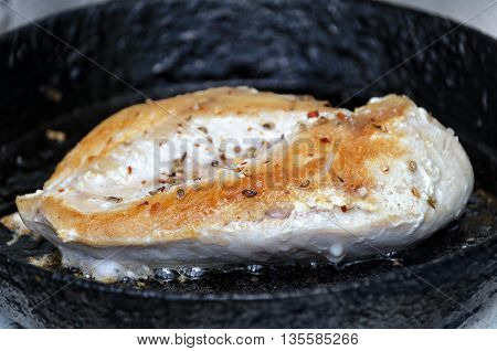 Grilled chicken breast on a cast iron old pan boiling oil